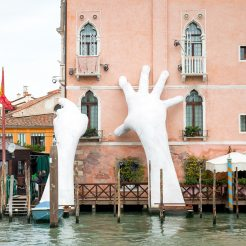 Huge replicas of human hands pretending to support a building