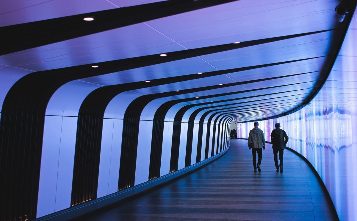 Two people walking in futuristic tunnel